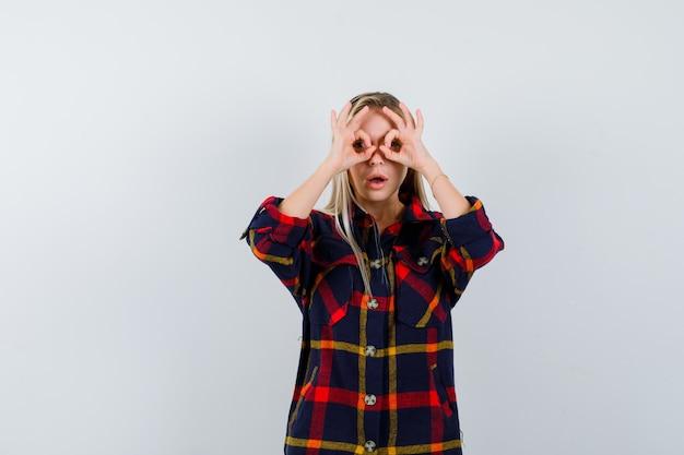 Jeune femme en chemise à carreaux montrant le geste de lunettes et regardant étonné, vue de face.