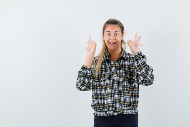 Jeune femme en chemise à carreaux montrant le geste ok et à la chance, vue de face.