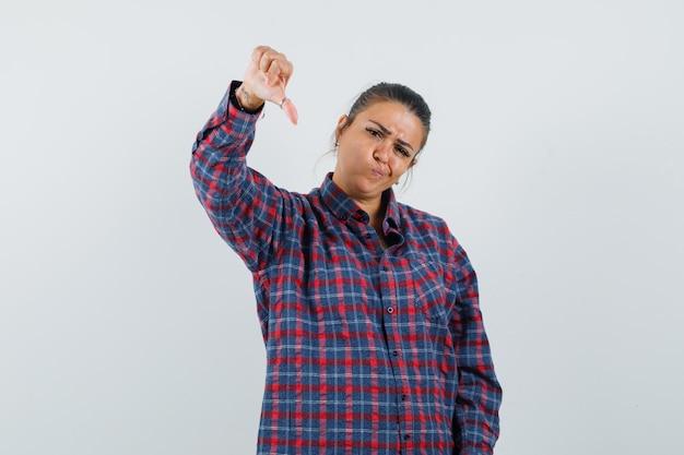 Jeune femme en chemise à carreaux montrant le pouce vers le bas et l'air mécontent, vue de face.