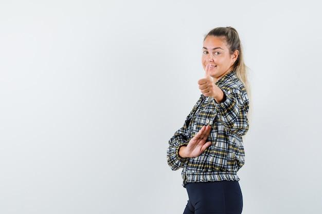 Jeune femme en chemise à carreaux montrant le pouce vers le haut et l'air confiant.