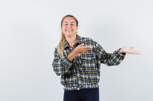 Jeune femme en chemise à carreaux montrant quelque chose et l'air heureux, vue de face.