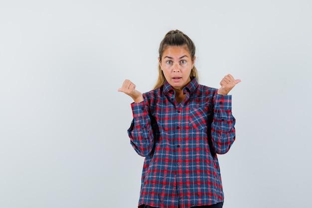 Jeune femme en chemise à carreaux pointant des directions différentes avec l'index et à la jolie