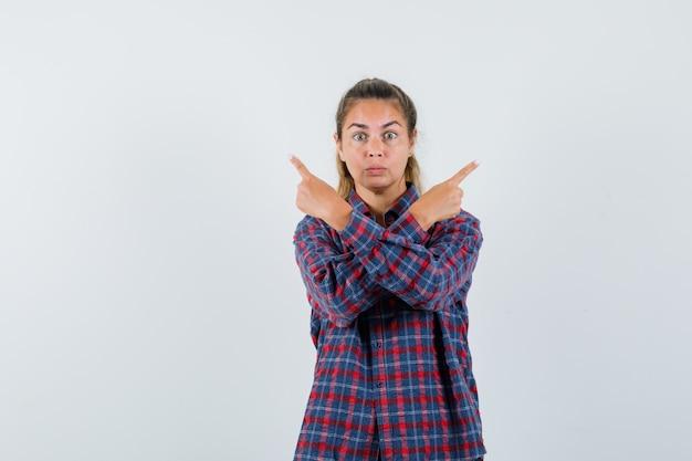 Jeune femme en chemise à carreaux pointant vers différentes directions et à la recherche de sérieux