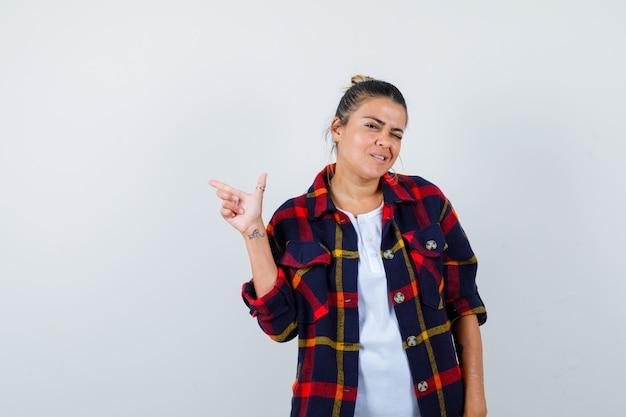 Jeune femme en chemise à carreaux pointant vers le haut et à la drôle, vue de face.