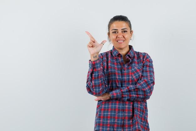 Jeune femme en chemise à carreaux pointant vers le haut à gauche avec l'index et à la jolie vue de face.