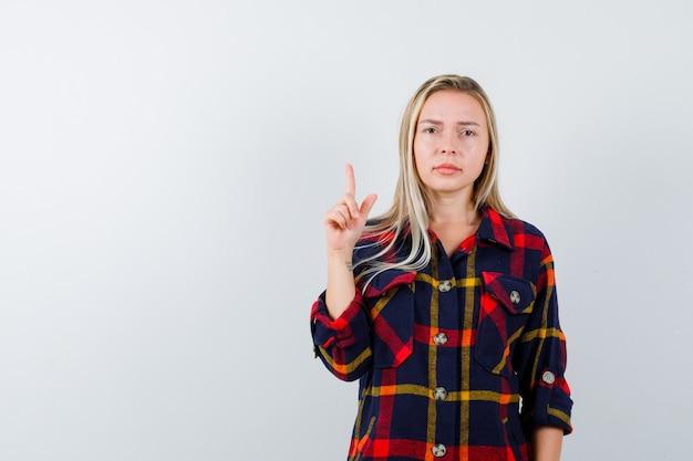Jeune femme en chemise à carreaux pointant vers le haut et à la vue de face, confiant.