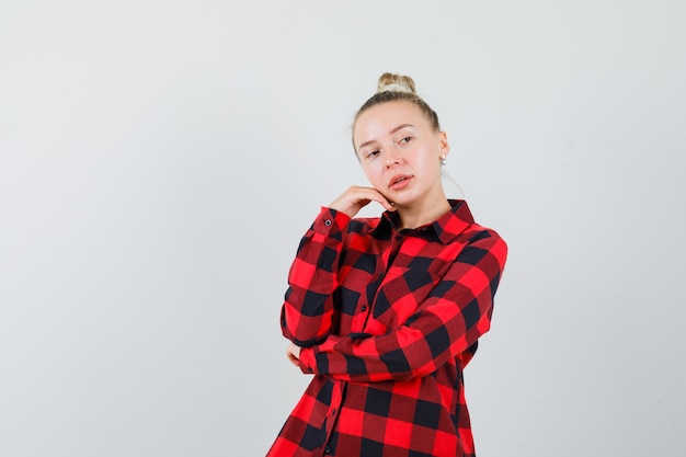 Jeune femme en chemise à carreaux posant tout en regardant ailleurs et à la charmante