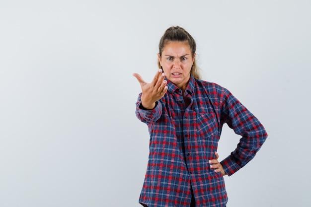 Jeune femme en chemise à carreaux qui s'étend de la main comme appeler quelqu'un tout en tenant une autre main sur la taille et à la colère
