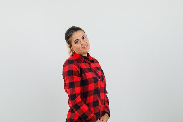 Jeune femme en chemise à carreaux regardant la caméra et regardant sensible, vue de face.