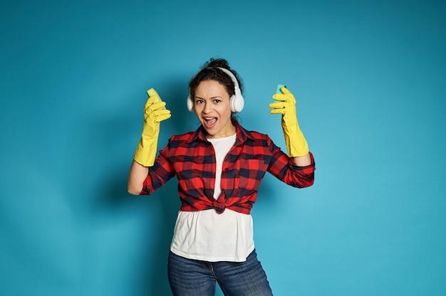 Jeune femme en chemise à carreaux rouge avec un casque sur sa tête chante, posant sur un bleu avec des éponges de nettoyage dans ses mains