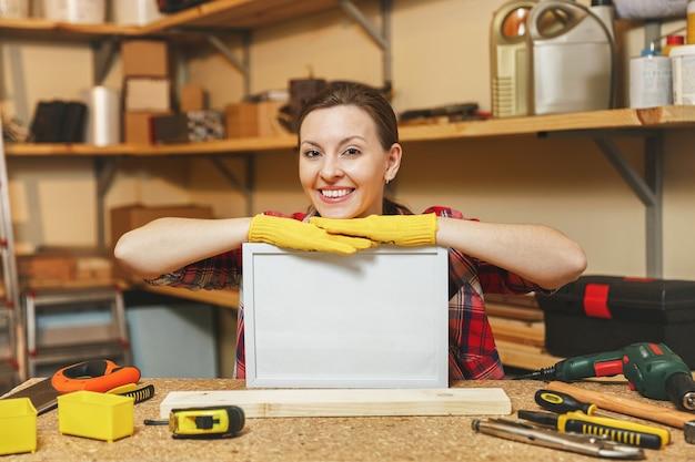 Jeune femme en chemise à carreaux, t-shirt gris, gants jaunes travaillant dans un atelier de menuiserie sur une table en bois avec cadre vierge, différents outils. avec une place vide pour le texte. copiez l'espace pour la publicité.