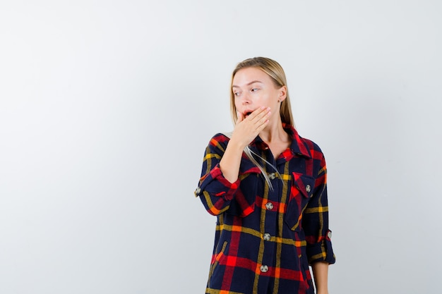 Jeune femme en chemise à carreaux tenant la main sur la bouche tout en regardant ailleurs et à la vue perplexe, de face.