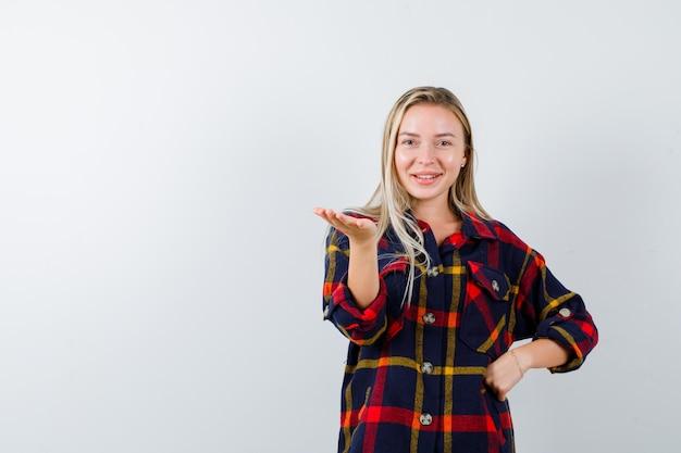 Jeune femme en chemise à carreaux tenant quelque chose tout en gardant la main sur la taille et à la joyeuse vue de face.