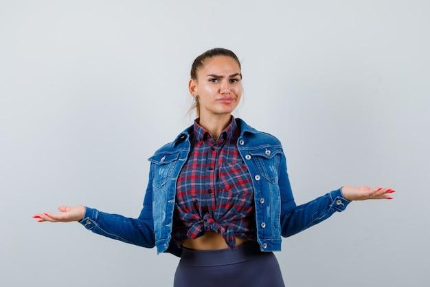 Jeune femme en chemise à carreaux, veste en jean écartant les bras et l'air mécontent, vue de face.