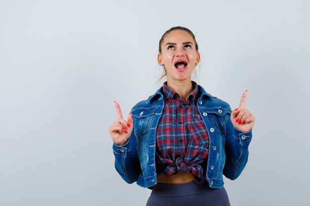 Jeune femme en chemise à carreaux, veste en jean pointant vers le haut et à la gaieté, vue de face.