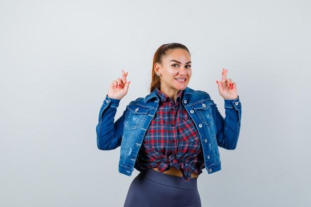 Jeune femme en chemise à carreaux, veste, pantalon montrant les doigts croisés et l'air joyeux, vue de face.