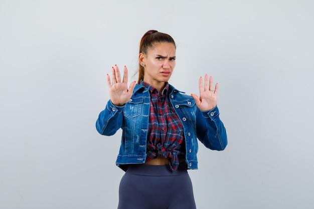 Jeune femme en chemise à carreaux, veste, pantalon montrant un geste d'arrêt et l'air sérieux, vue de face.