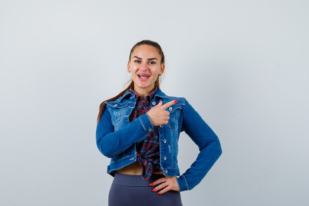 Jeune femme en chemise à carreaux, veste, pantalon pointant vers le côté droit tout en gardant la main sur la hanche et l'air étonné, vue de face.