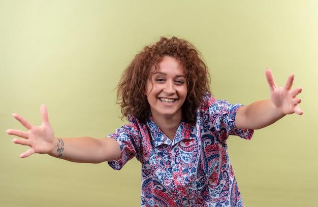 Jeune femme en chemise colorée ouvrant les mains larges souriant sympathique faisant le geste de bienvenue debout sur le mur vert