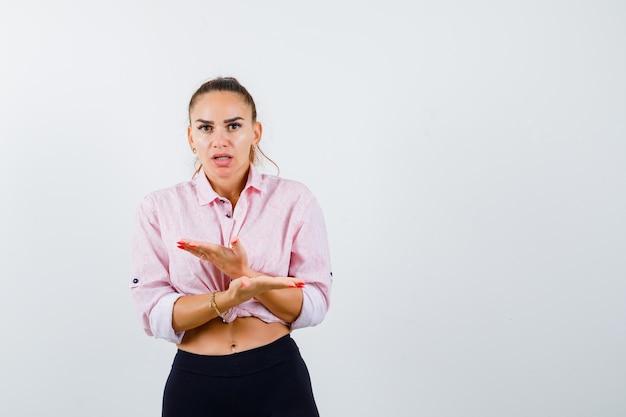 Jeune femme en chemise décontractée montrant quelque chose avec les mains croisées et à la vue de face, hésitante.