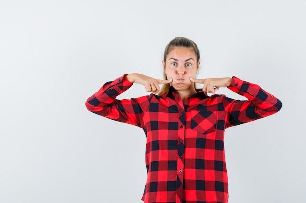 Jeune femme en chemise décontractée tenant les doigts sur les joues soufflées et à la drôle, vue de face.