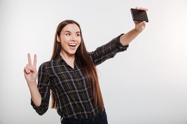 Jeune femme en chemise faisant selfie sur téléphone
