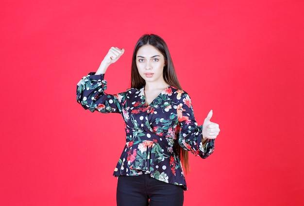 Jeune femme en chemise à fleurs debout sur un mur rouge et démontrant les muscles de ses bras