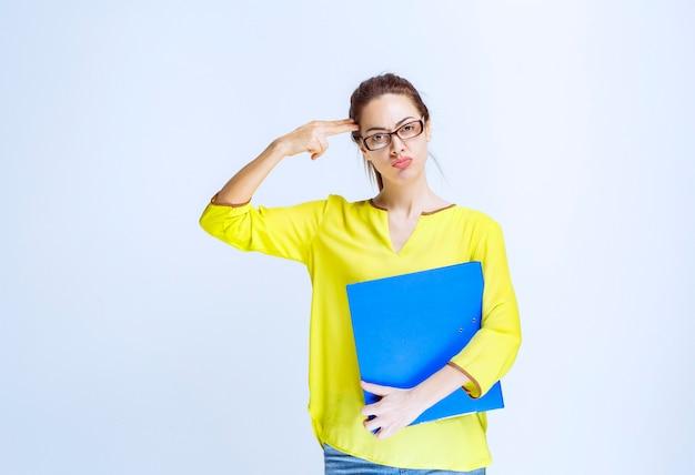La jeune femme en chemise jaune a l'air réfléchie et rêveuse