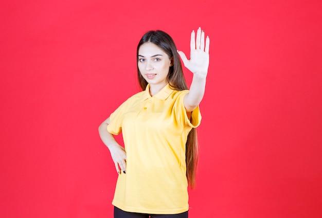 Jeune femme en chemise jaune debout sur un mur rouge et arrêter quelque chose