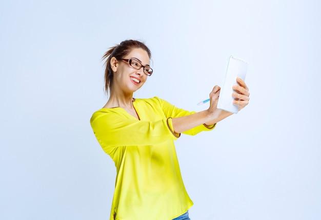 Jeune femme en chemise jaune prenant ses notes pendant que le professeur parle