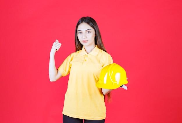 Jeune femme en chemise jaune tenant un casque jaune et montrant quelqu'un derrière