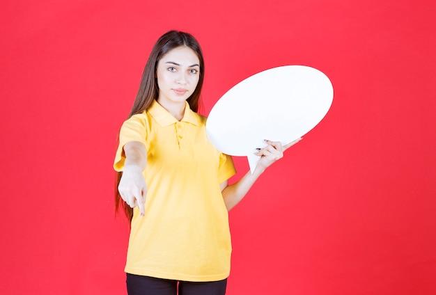 Jeune femme en chemise jaune tenant un panneau d'information ovale et invitant son collègue à côté d'elle