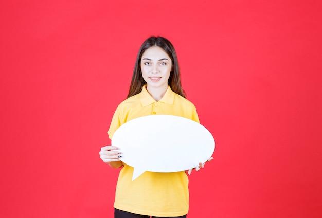 Jeune femme en chemise jaune tenant un panneau d'information ovale