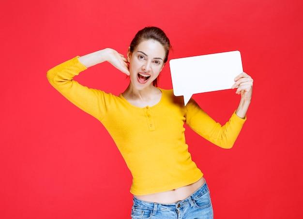 Jeune femme en chemise jaune tenant un panneau d'information rectangle
