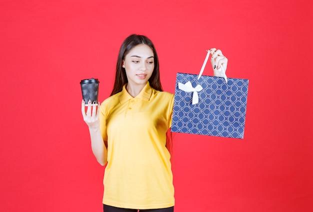 Jeune femme en chemise jaune tenant un sac bleu et un gobelet jetable noir de boisson