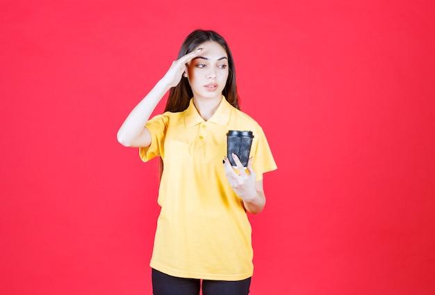 Jeune femme en chemise jaune tenant une tasse de café jetable noire, pensant et ayant une bonne idée