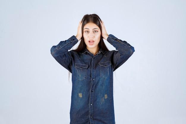 Jeune femme en chemise en jean a l'air effrayé et effrayé