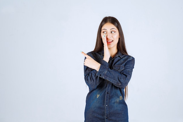 Jeune femme en chemise en jean chuchotant et bavardant