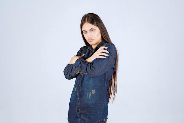 Jeune femme en chemise en jean donnant des poses neutres sans réactions