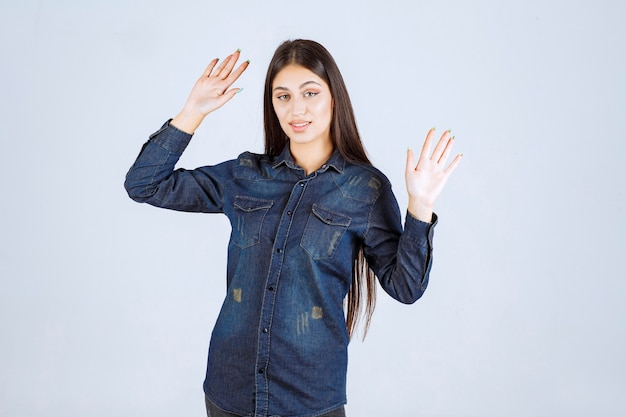 Jeune femme en chemise en jean essayant d'empêcher et d'arrêter quelque chose