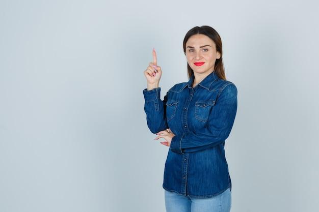 Jeune femme en chemise en jean et jeans pointant vers le haut et à la joie