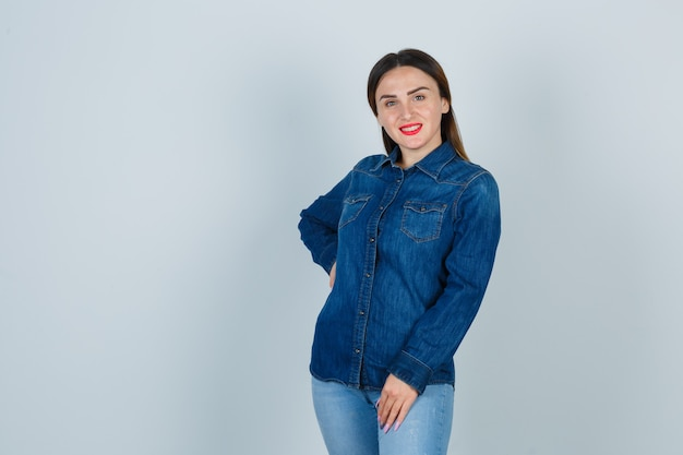 Jeune femme en chemise en jean et jeans tenant la main sur la hanche tout en posant et à la charmante