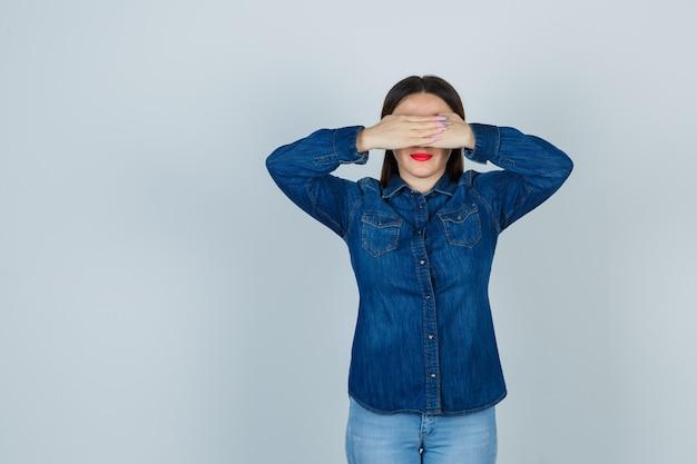Jeune femme en chemise en jean et jeans tenant les mains sur les yeux et à la recherche de sérieux