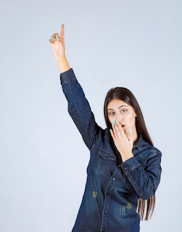 Jeune femme en chemise en jean levant les mains et montrant quelque chose au-dessus
