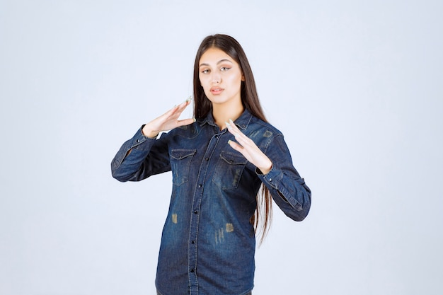 Jeune femme en chemise en jean montrant les mesures d'un objet