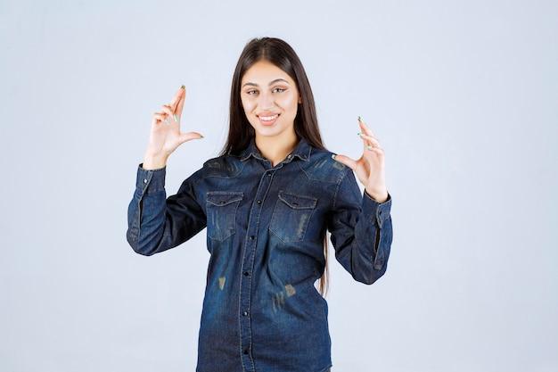 Jeune femme en chemise en jean montrant les mesures d'un produit