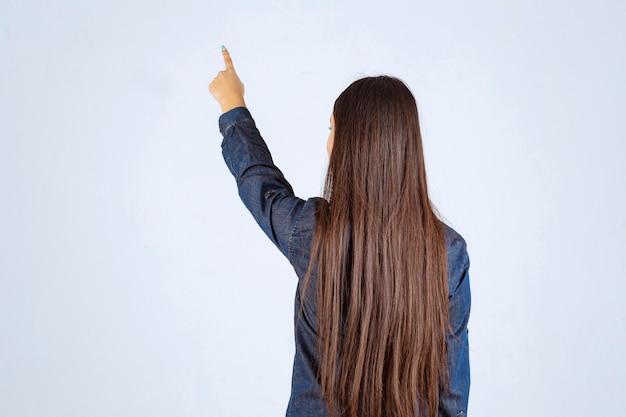 Jeune femme en chemise en jean montrant quelque chose derrière
