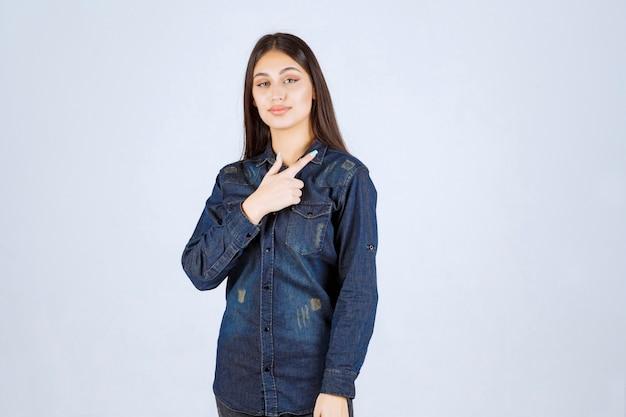 Jeune femme en chemise en jean montrant quelque chose sur la droite