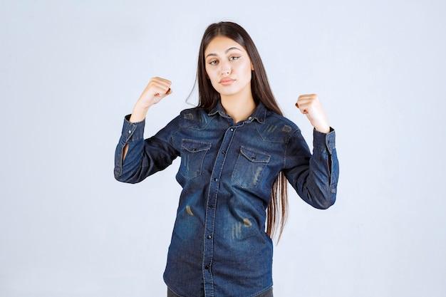 Jeune femme en chemise en jean montrant ses muscles du bras