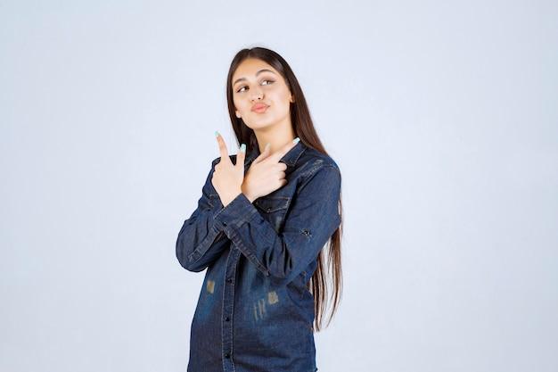 Jeune femme en chemise en jean pointant des deux côtés